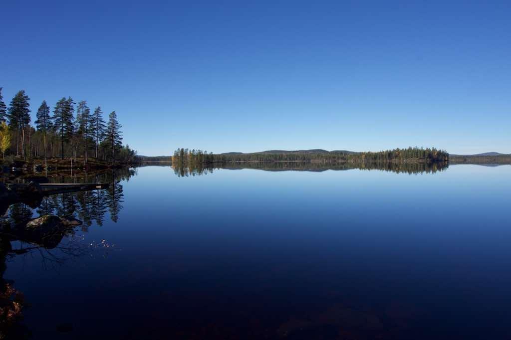 Zo'n strakblauwe lucht weerkaatst schitterend in een spiegelglad meer.