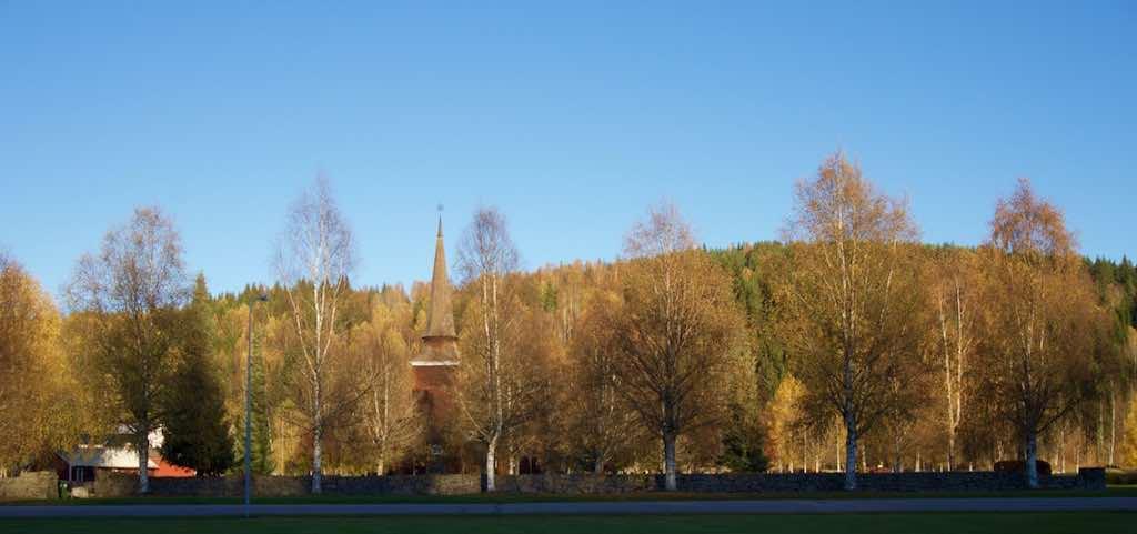 De houten kerk valt bijna niet meer op tussen de herfstkleuren.