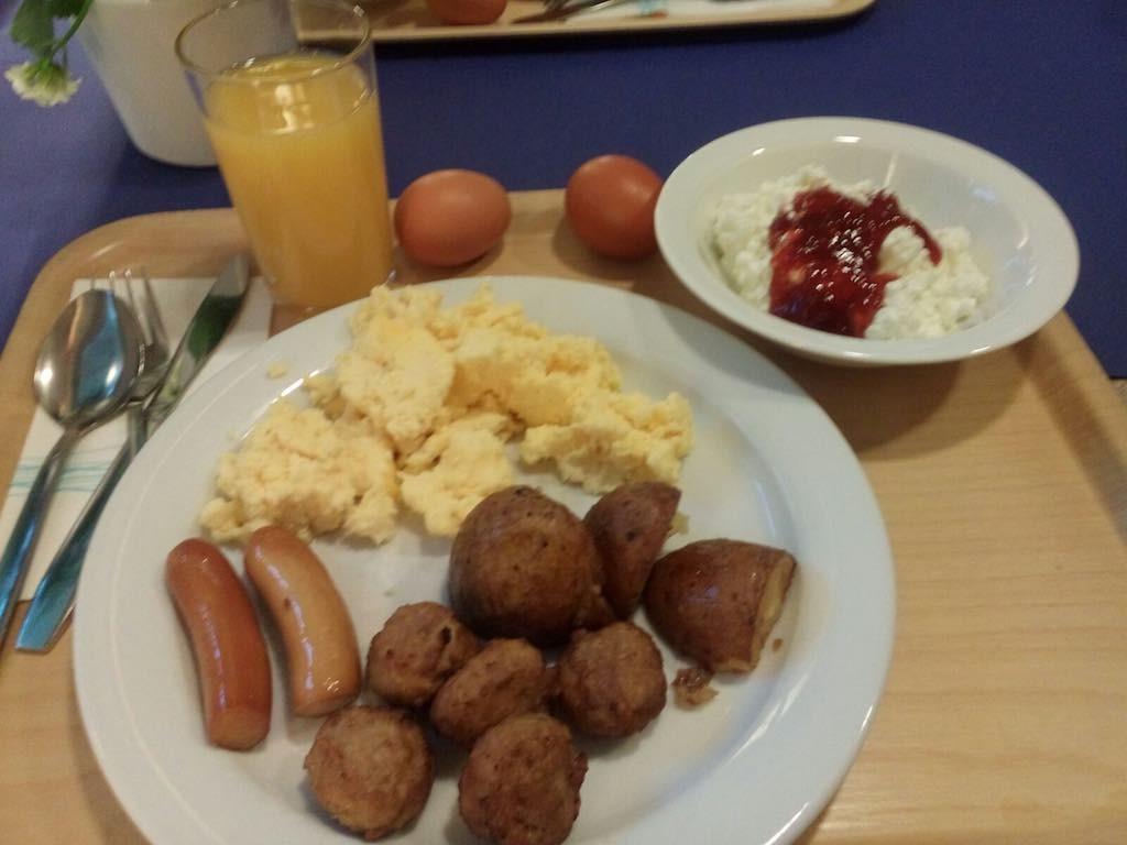 Ontbijt van Emma, roerei, worstjes, gehaktballetjes, aardappelen, gekookte eieren, kwark en een sapje.